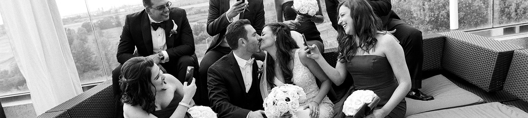 Photo of a married couple kissing around their friends