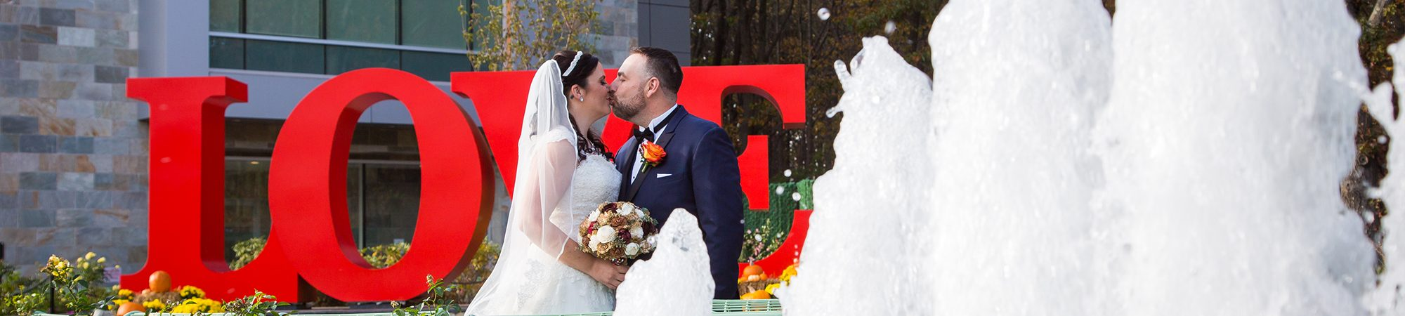 Happy couple kissing in front of LOVE sculpture