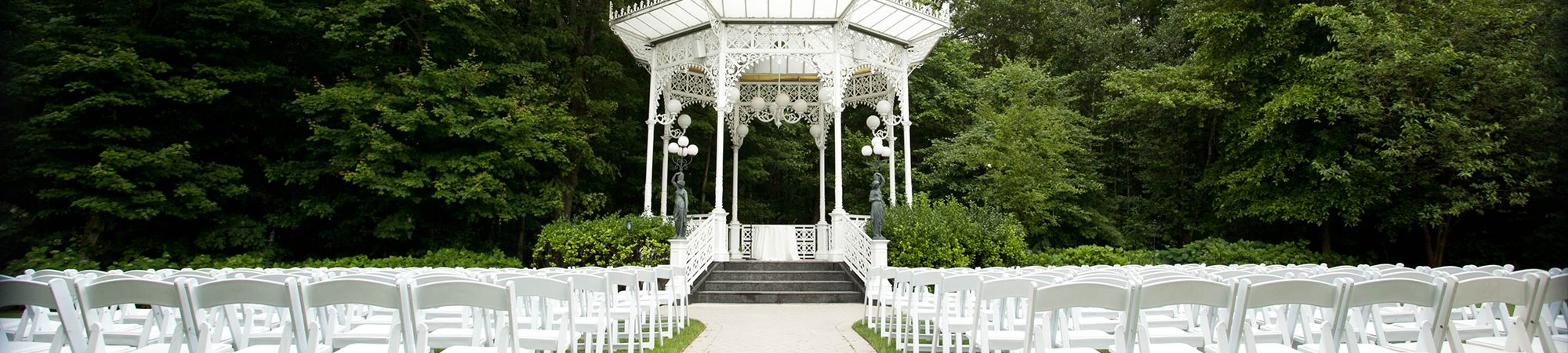 Green trees around white wedding aisle